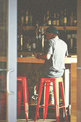 Man sitting on a red stool eating